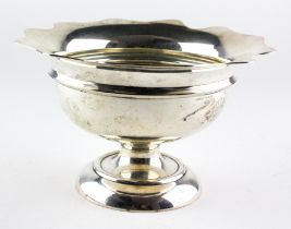 An Edwardian silver bowl raised on footed base, with flowing border,