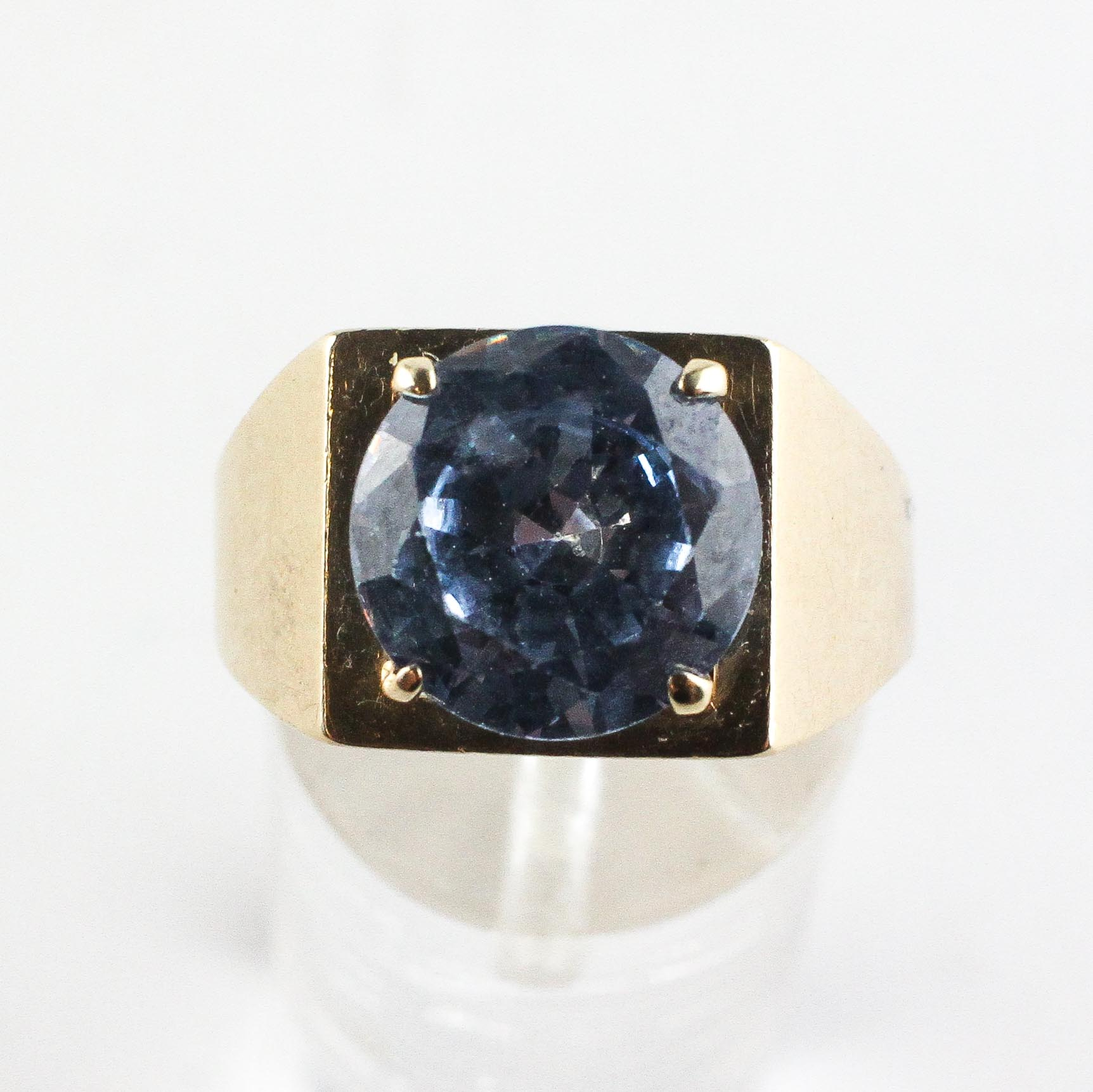 A yellow metal ring set with a 10mm round cut synthetic blue spinel. - Image 2 of 4