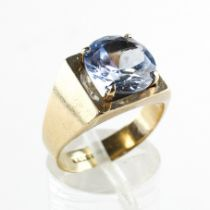 A yellow metal ring set with a 10mm round cut synthetic blue spinel.