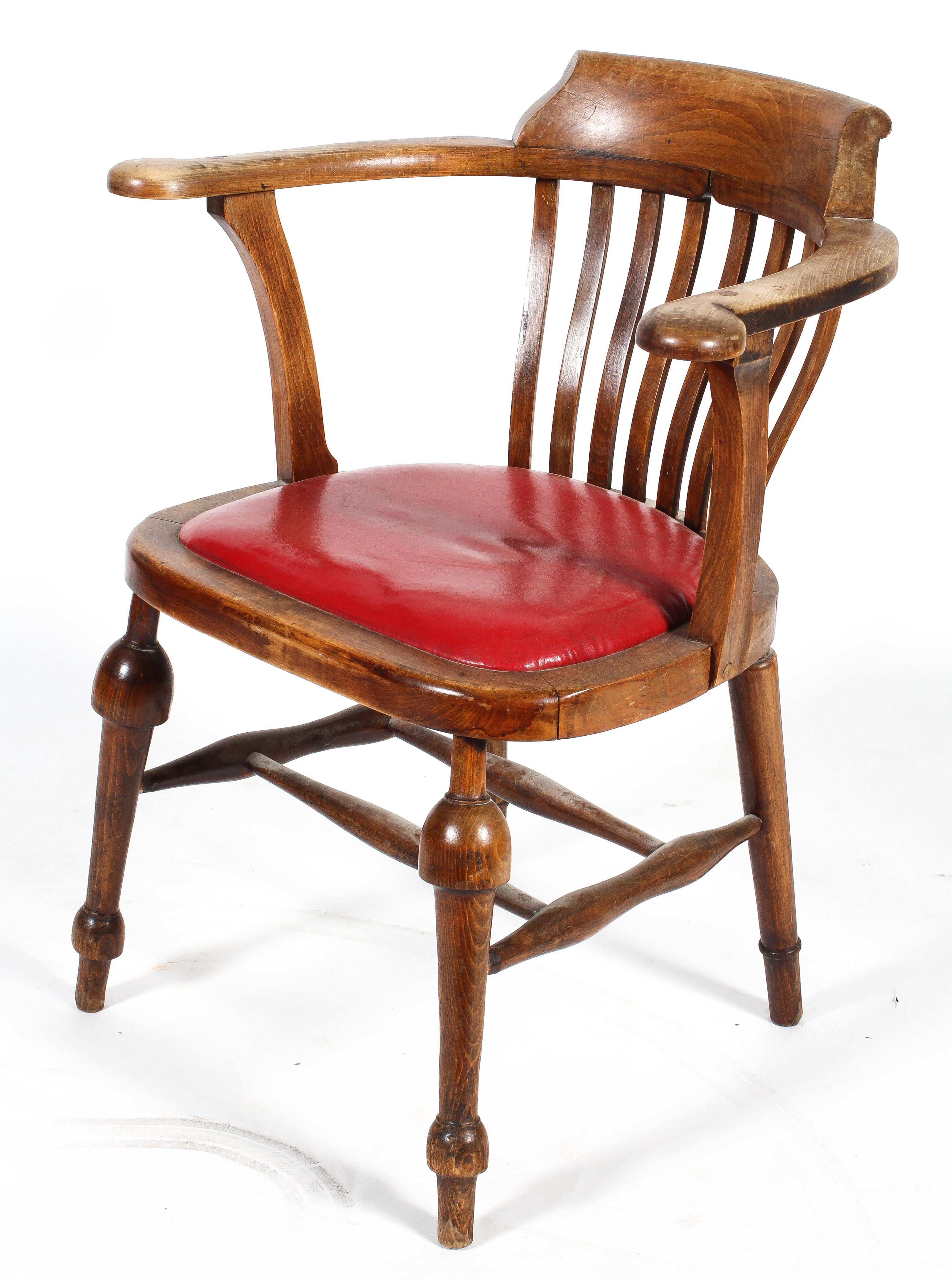 An Edwardian elm desk chair, with lathe back and padded seat,