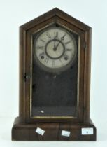 A mid century American mantel clock, wooden cased, the dial with Roman numerals denoting hours,