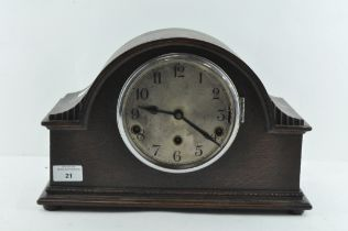 An oak cased mantle clock, the dial with Arabic numerals denoting hours,