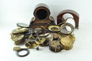 A collection of clock parts, including movements, cases and dials,