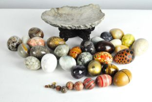 A collection of assorted vintage stone eggs, various designs and materials,