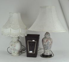 Two lamps and a leather bin, the lamps printed or moulded with flowers, with cream coloured shade,