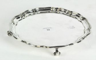 A 20th century silver plated salver retailed by 'Harrods' raised upon scrolling feet,