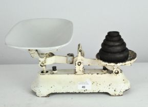 A set of vintage scales, the white metal frame supporting an enamel dish and a set of five weights,