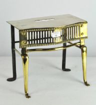 An ornate brass trivet stand, with pierced grill to front, on flowing feet