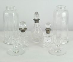 A group of three cut glass bottles with glass storm lanterns and a pair of glass candlestick bases