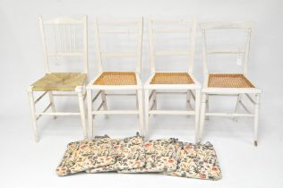 Four vintage painted white chairs, three with wicker seats,