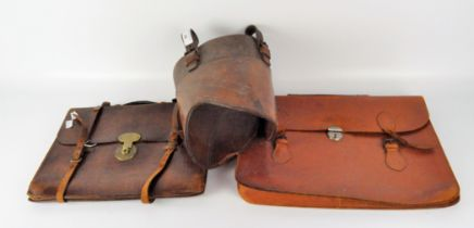Two brown leather briefcases with metal fastenings;