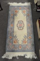 A small Chinese rug, 20th century, woven with flowers on ivory cream ground,