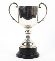 A sterling silver trophy with loop handles on a circular stepped base. with turned ebonised stand.
