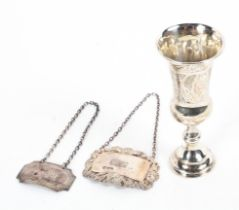 Two sterling silver decanter labels together with a small sterling silver communion cup,