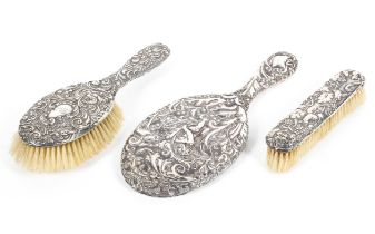 A sterling silver backed brush set with raised acanthas leaf decoration.