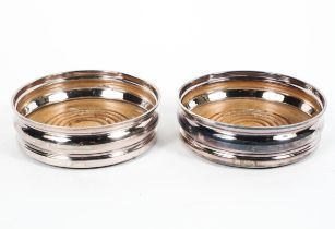A pair of sterling wine bottle coasters with turned wooden bases. by Nat Joseph Birmingham, 1966.
