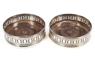 A pair of Georgian sterling silver wine bottle coasters with turned wooden bases, London,