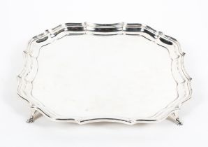 A sterling silver salver or card tray of square form with gadrooned border raised on four feet.