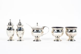 A sterling silver condiment set comprising: two salts and a mustard pot with blue glass liners