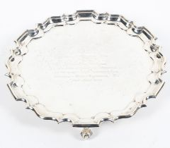 A sterling silver circular salver or card tray with pie crust border raised on three scrolling feet.