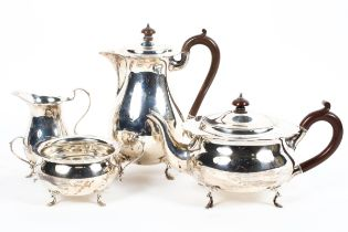 A four piece sterling silver tea set of circular form with flared rim each piece raised on four