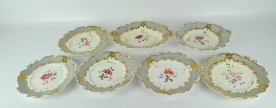 Six Victorian Rococo style plates and a serving platter, all with scrolling edges,