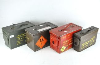 A group of four metal ammunition cases,