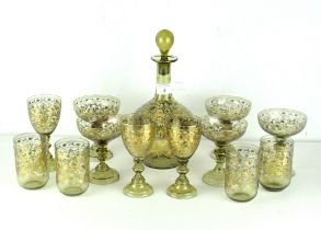 An ornate green glass decanter set, inlaid with flowing gilt floral sprays.