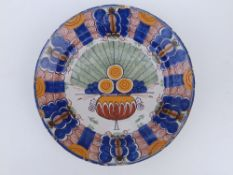 An 18thC polychrome delft charger, decorated with a stylised peacock medallion to centre, in blue,
