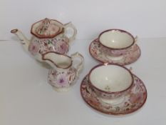Six pieces of dolls' Victorian tea china, decorated in pink lustre flowers, comprising; a teapot,