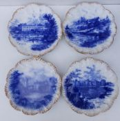 A set of four flow blue pottery plates with gilt scalloped borders, decorated with 'castle' scenes