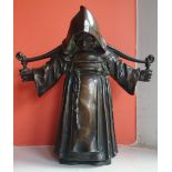 """An antique bronze figure study of a monk carrying a yoke over his shoulders, 10"""" high."""