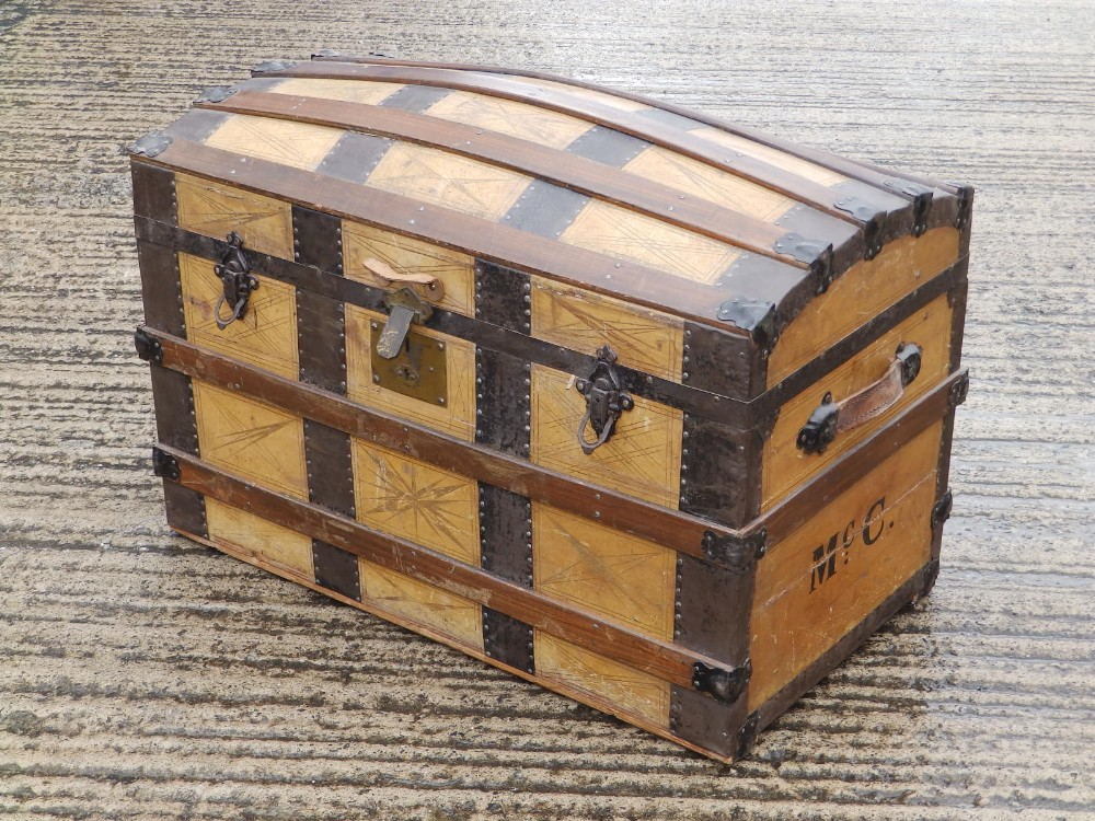 """A domed wooden bound cabin trunk with paper lined interior compartments, 32"""" across."""