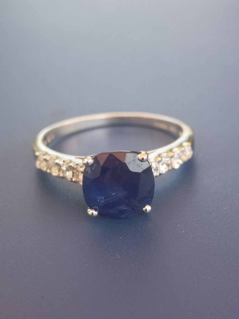 A modern sapphire solitaire ring, in four claw setting with small diamonds to shoulders, 14ct