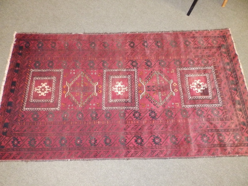 A Baluchi rug, the centre occupied by three rectangles and two octagons with small animal motifs,