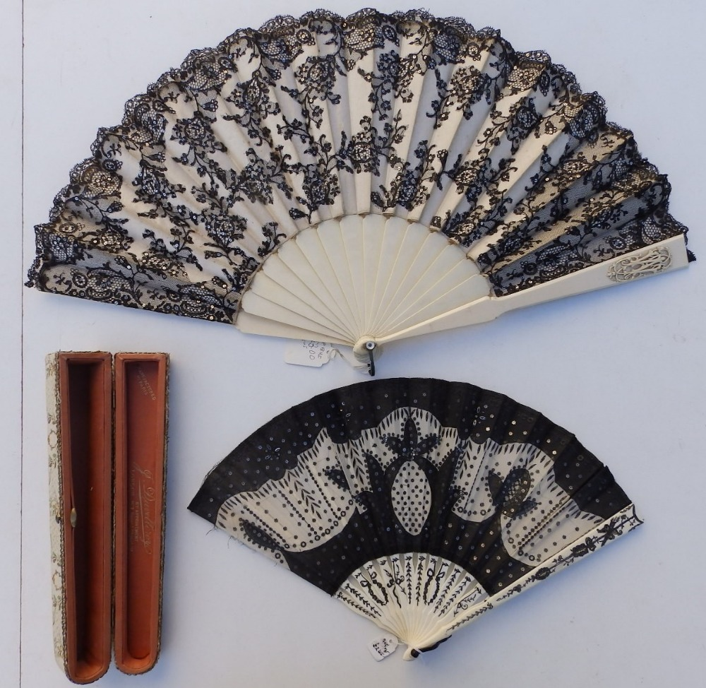 A 19thC ivory fan, the cream silk leaf decorated in black lace with sequins, an openwork monogrammed