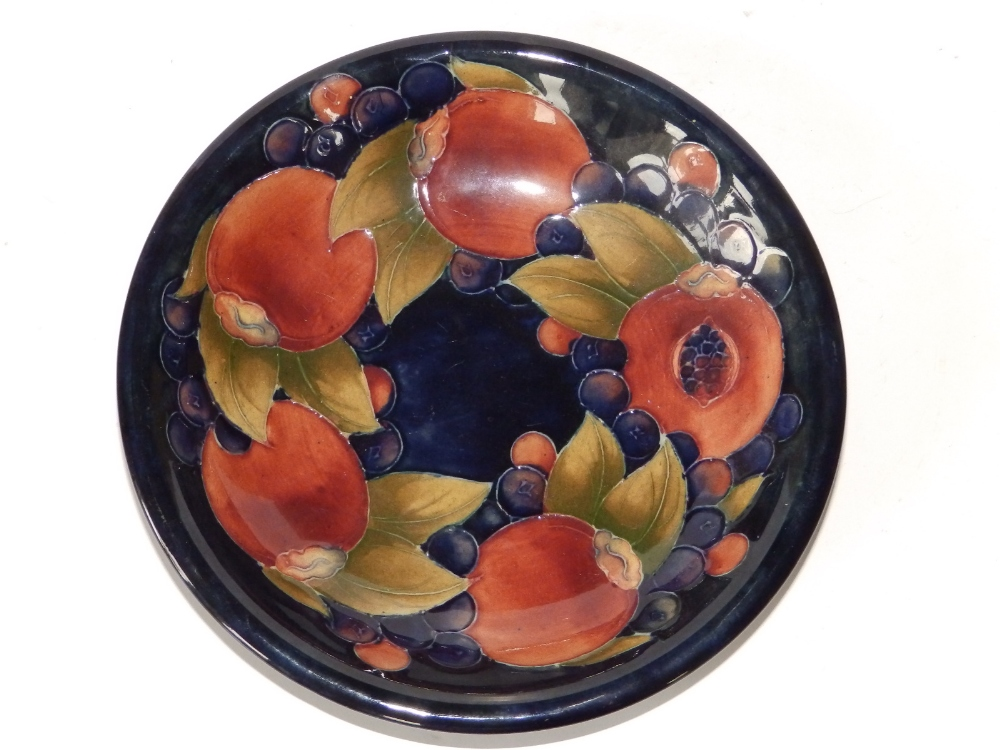 """A Moorcroft Pomegranate dish - 'Potter to HM The Queen', paper label & impressed, 7.4"""" diameter."""