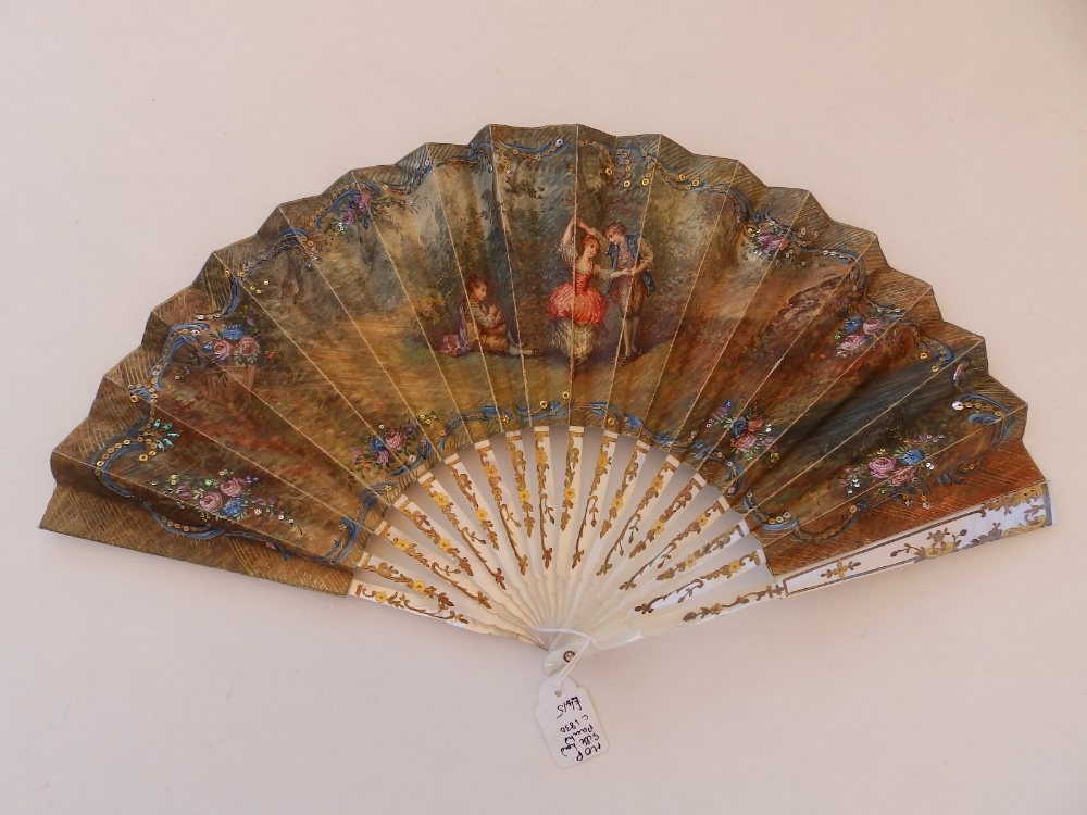 An early 19thC mother-of-pearl fan, the paper leaf painted with a young dancing couple to one