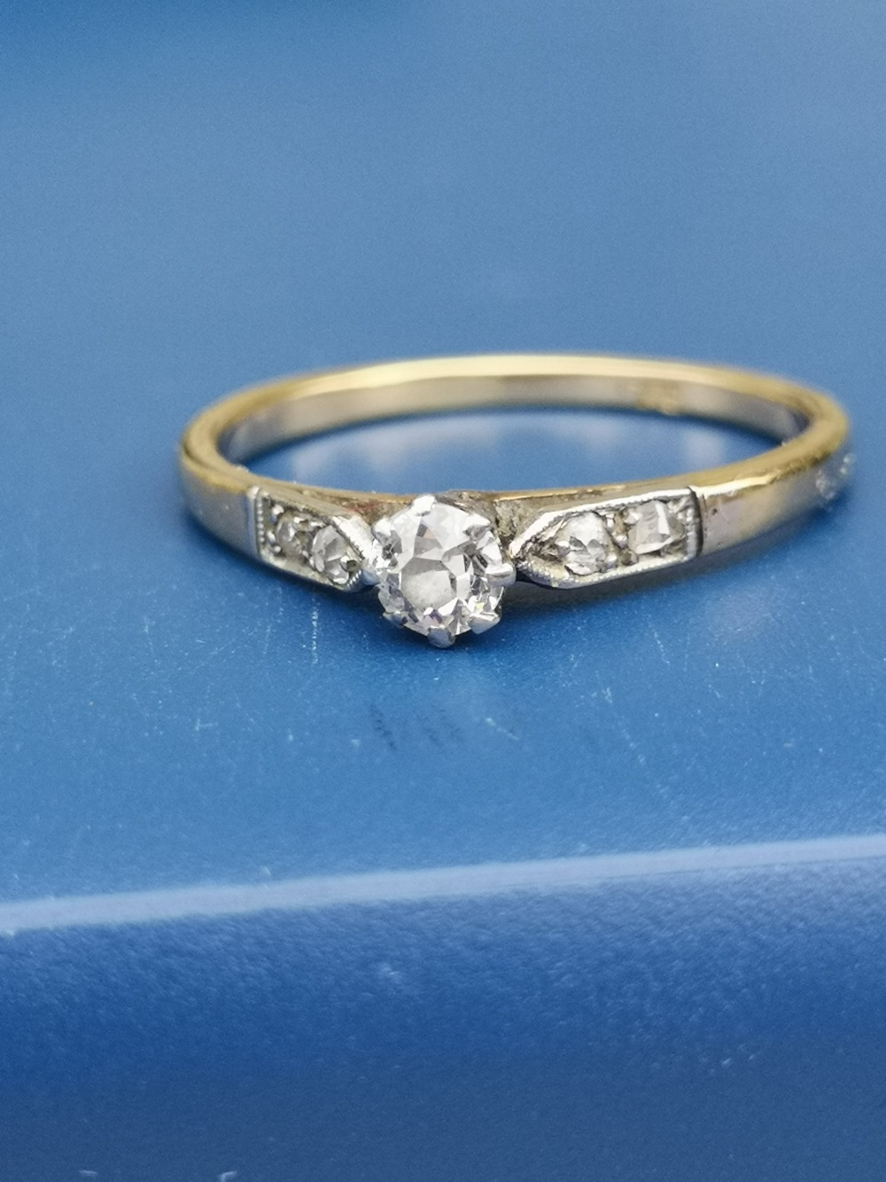 A small old cut diamond solitaire ring, diamonds to shoulders, on 18ct gold shank. Finger size P.