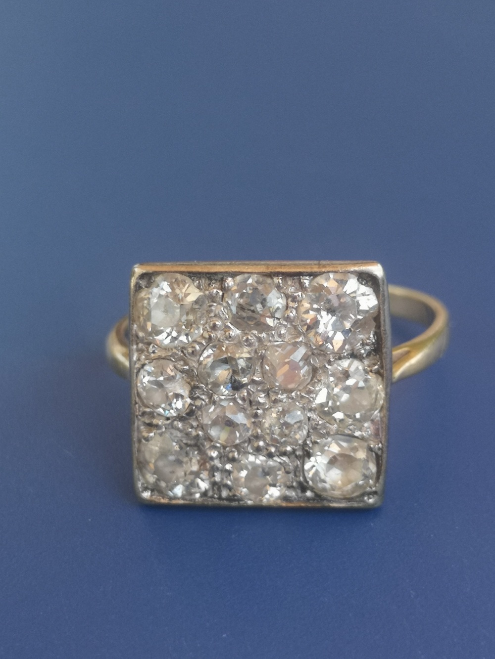 A diamond dress ring having a square pave setting on yellow metal shank. Finger size L.