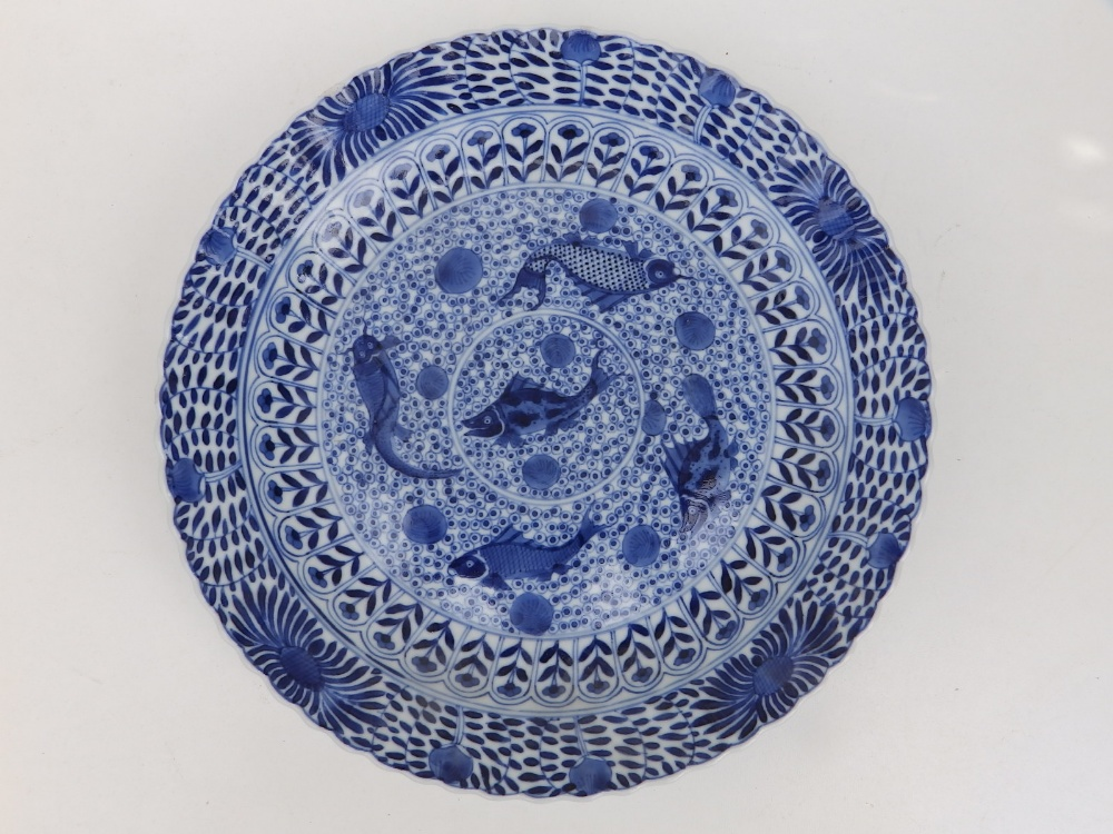 A Chinese blue & white porcelain plate decorated with five small carp against an ornamental