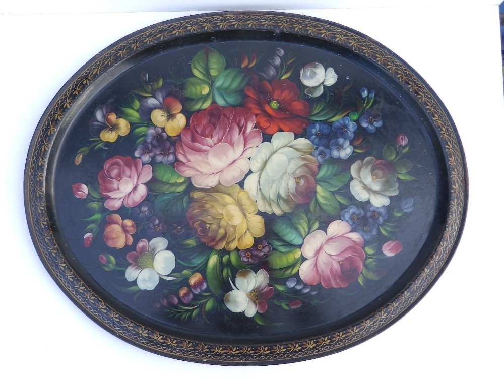 """An oval painted metal Russian tray decorated flowers on black ground, 20"""" across."""
