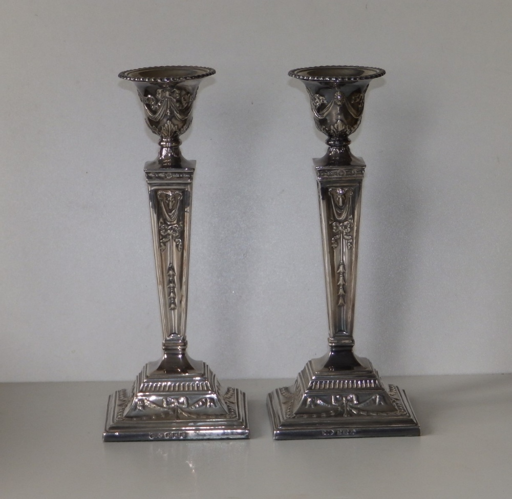 A pair of modern silver candlesticks, of square neoclassical form with detachable beaded sconces,