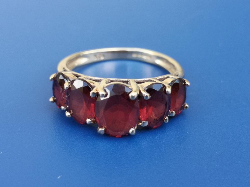 A graduated garnet set 9ct gold ring. Finger size L/M.