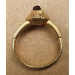 A 15thC silver-gilt finger ring with square cut garnet.