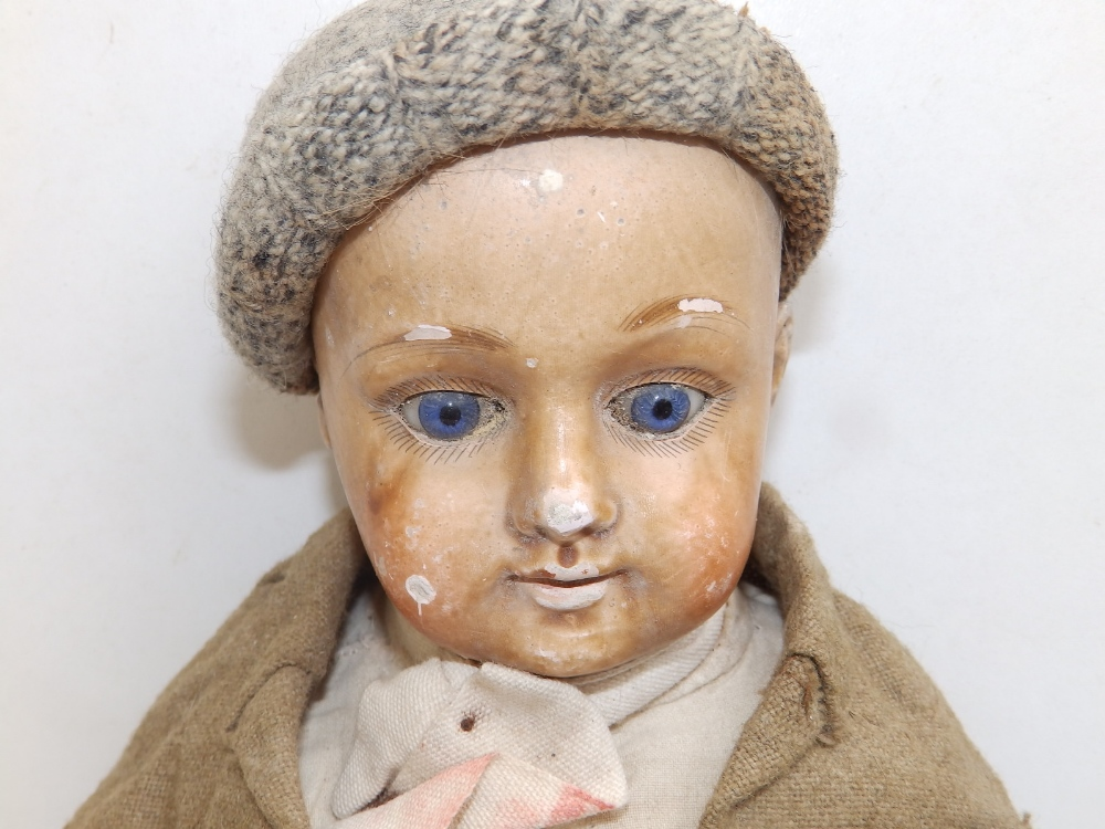"""A wax-headed boy doll with blue paperweight eyes, 18"""" overall."""