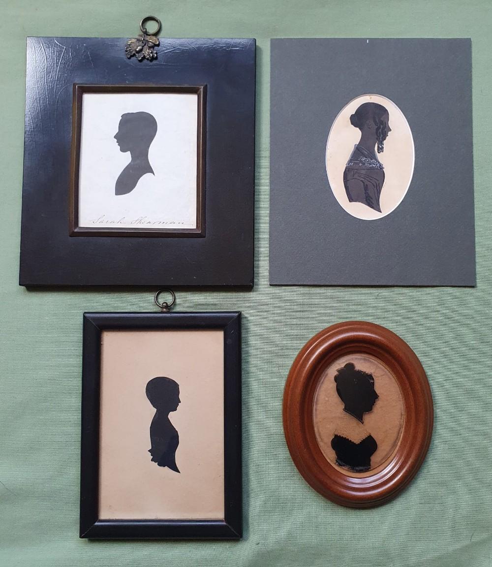 Four framed silhouette portraits.