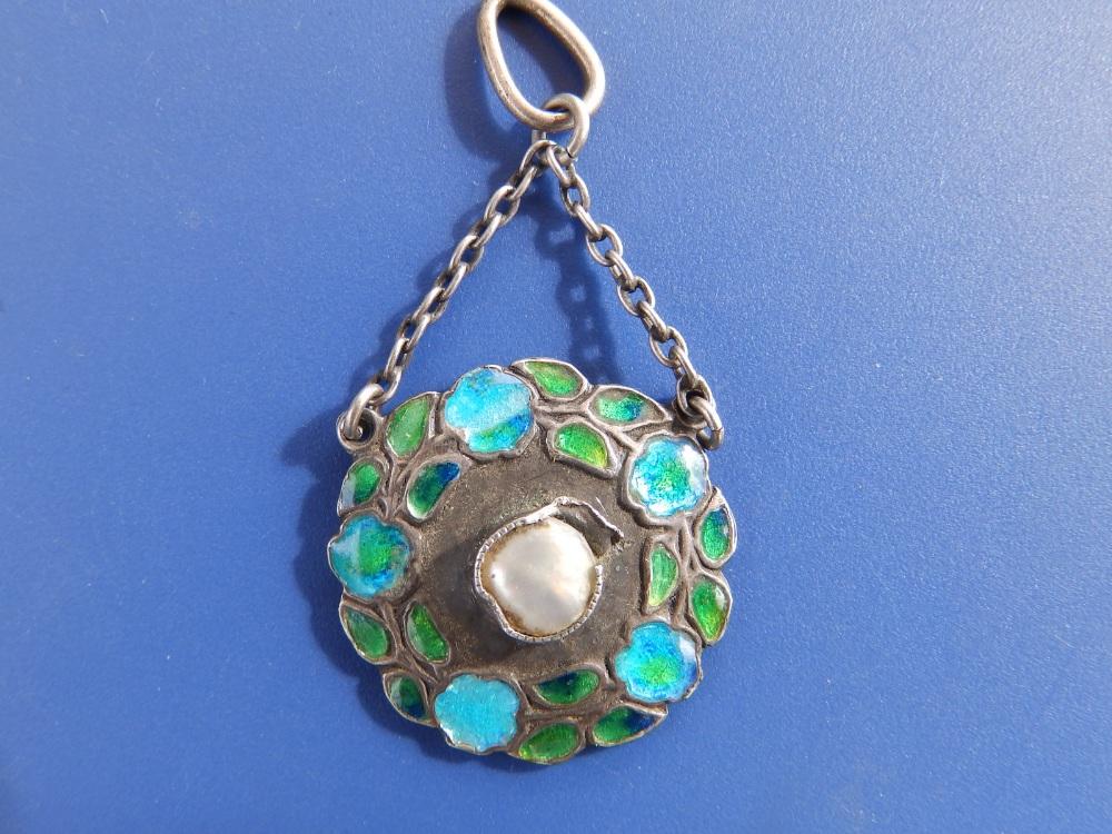 An enamelled 950 silver art nouveau pendant by Murrle Bennett & Co, of circular flower garland