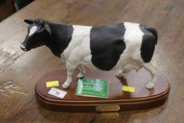 Royal Doulton Fresian cow ornament on wood plinth
