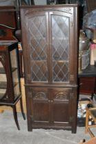 A reproduction glazed oak double corner